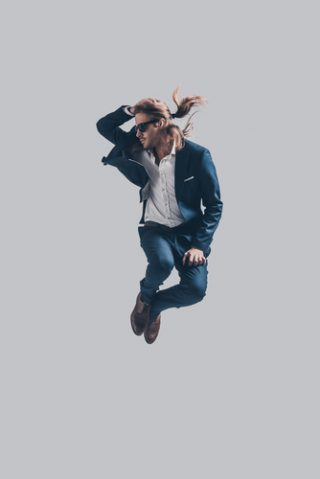 Feeling comfortable in his style. Handsome young man in full suit and sunglasses jumping against grey background
